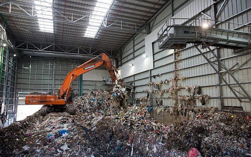 Un bulldozer soulève des déchets à l'usine de recyclage de Greenet, dans la zone industrielle d'Atarot, au nord de Jérusalem, le 16 juin 2015 (Crédit : Yonatan Sindel/Flash90)