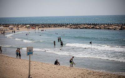 Israéliens et touristes à la plage de Tel Baruch à Tel Aviv, le 10 juillet 2019. (Crédit : Yonatan Sindel/Flash90)