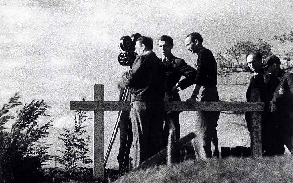 Une équipe de tournage réalise des prises de vue dans le ghetto de Theresienstadt lors du tournage d'un film de propagande nazie en 1944. Un assistant juif portant une étoile de David est à droite. (Domaine public)