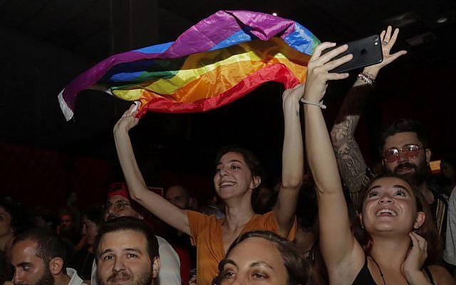 Une femme brandit un drapeau arc-en-ciel lors d'un concert organisé en solidarité avec le groupe indie libanais Mashrou 'Leila à Beyrouth, la capitale du Liban, le 9 août 2019. (Crédit : Anwar Amro / AFP)