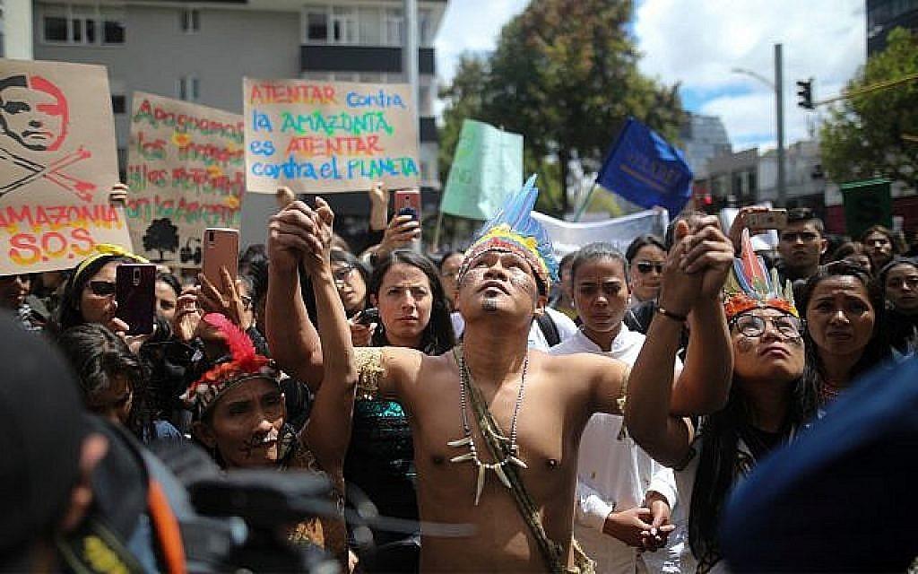 Des manifestants indigènes lors d'un rassemblement aux abords de l'ambassade du Brésil appelant le président Jair Bolsonaro à agir pour la protection de la forêt amazonienne à Bogota, en Colombie, le 23 août 2019 (Crédit : AP Photo/Ivan Valencia)