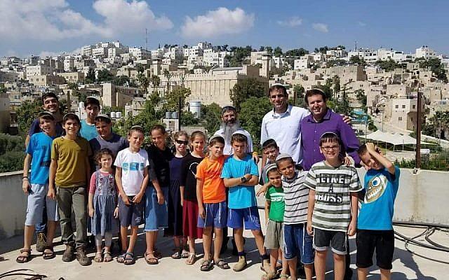 Des habitants d'implantation sur le toit d ela maison Machpela à Hébron après avoir réinvesti le bâtiment pour la première fois depuis des mois, le 25 août 2019. (Crédit : mouvement Harhivi)