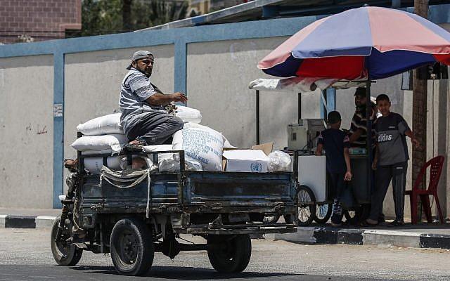 Un Palestinien se trouve sur un pickup transportant un sac d'aide alimentaire fourni par l'UNRWA au sud de Gaza ville à Rafah, le 25 juin 2019. (Said Khatib/AFP)