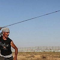 Un émeutier palestinien utilise une fronde pour lancer des pierres sur les forces israéliennes à proximité de la barrière de la frontière avec Israël dans la bande de Gaza, le 16 août 2019. (Photo de MAHMUD HAMS / AFP)