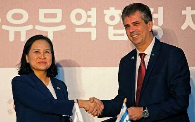 La ministre sud-coréenne du Commerce Yoo Myung-hee (gauche) et le ministre israélien de l'Economie et l'Industrie Eli Cohen se serrent la main après avoir signé un accord de libre échange entre Israël et la République de Corée à Jérusalem, le 21 août 2019. (Photo de Gil COHEN-MAGEN / AFP)