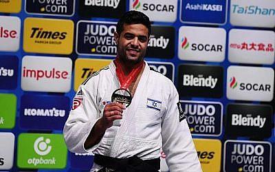 Le médaillé d'or israélien Sagi Muki prend la pause sur le podium de la catégorie homme des -81kg lors du Championnat du monde de judo à Nippon Budokan, le site où auront lieu les prochains Jeux Olympiques, à Tokyo, le 28 août 2019. (CHARLY TRIBALLEAU / AFP)