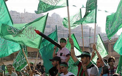 Des Palestiniens agitant des drapeaux du Hamas  et scandent des slogans lors d'une fête organisée par le Hamas dans la ville cisjordanienne de Naplouse, le vendredi 29 août 2014. (AP/Nasser Ishtayeh)
