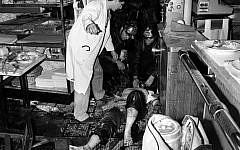 Des pompiers et des infirmières s'occupent d'un blessé derrière le comptoir d'un restaurant juif Jo Goldenberg, situé dans la rue des Rosiers à Paris, après l'attaque terroriste perpétrée par des hommes armés dans le restaurant, le 9 août 1982. L'attaque a fait six morts et de nombreux blessés. (AP Photo/ Aulnay)