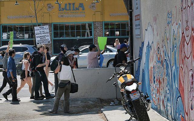 Des manifestants portent des pancartes pour dénoncer le racisme dans la rue principale de la zone de Venice Beach à Los Angeles, le dimanche 19 août 2017. (AP Photo/Richard Vogel)