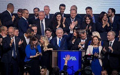 Le Premier ministre Benjamin Netanyahu, entouré par des politiciens du Likud et sa femme Sara, s'adresse à ses partisans alors que les résultats des élections israéliennes sont annoncés, au quartier général du parti à Tel Aviv, tôt le 10 avril 2019. (Yonatan Sindel/FLASH90)