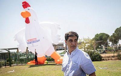 Simcha Goldin, le père du soldat israélien mort au combat Hadar Goldin, se trouve à côté d'un coq gonflable de 10 mètres de haut lors d'une manifestation devant la Knesset le 14 août 2019. (Hadas Parush/Flash90)
