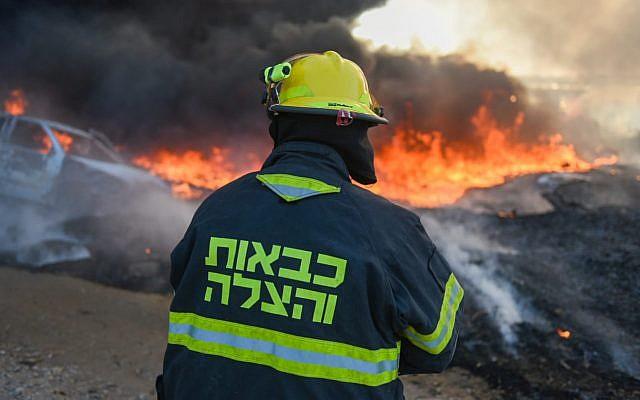Un pompier travailler à éteindre un incendie causé par un engin explosif lancé depuis la bande de Gaza vers le sud d'Israël, le 27 juin 2019. (Crédit : pompiers israéliens)