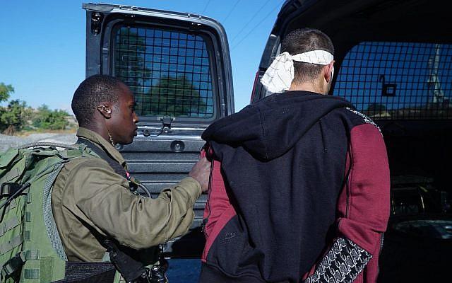 Un des suspects (à droite) du meurtre de Dvir Sorek après avoir été arrêté par la Police aux Frontières et Tsahal en Cisjordanie le 10 août 2019. (Crédit : Armée israélienne)
