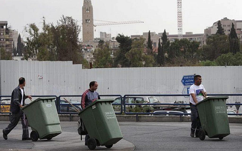 Trois hommes poussent des poubelles vertes à Jérusalem, le 27 octobre 2009 (Crédit : Nati Shohat/FLASH90)