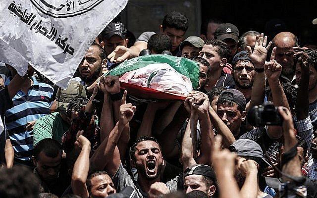 Des Palestiniens transportent le corps d'un tireur d'élite du Hamas tué par les tirs israéliens, lors de ses funérailles à Jabalia, dans le nord de la bande de Gaza, le 7 août 2018. (AFP/MAHMUD HAMS)