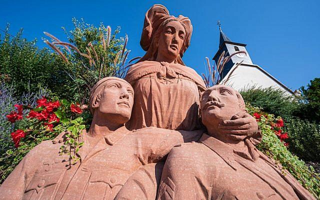 Une photographie prise le 23 août 2019 montre le mémorial de grès du village alsacien de Wintzenbach, considéré comme un monument unique en Alsace puisqu'il montre un soldat français (R) et un soldat allemand (L) réunis dans les bras de sa mère alsacienne. (Crédit : PATRICK HERTZOG / AFP)