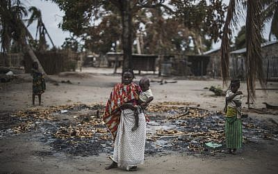 Une femme tient son enfant dans une région brûlée après une récente attaque du village d'Aldeia da Paz au Mozambique, le 24 août 2019. (Crédit : MARCO LONGARI / AFP)