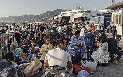 Des réfugiés et migrants attendent d'embarquer sur l'île de Lesbos, le 2 septembre 2019. (Crédit : STRINGER / AFP)