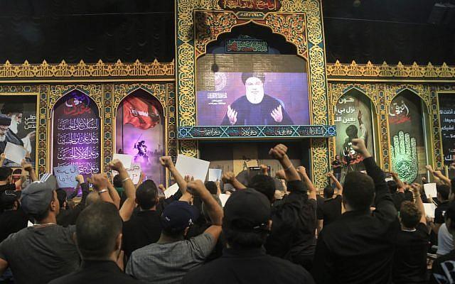 Les partisans du groupe terroriste chiite libanais Hezbollah réagissent avec les poings serrés en regardant le discours du leader du mouvement Hasan Nasrallah, transmis sur grand écran dans la banlieue sud de Beyrouth, la capitale libanaise, le 2 septembre 2019. (Photo par l'AFP)