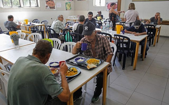 Des personnes défavorisées déjeunent à Lasova, une soupe populaire à Tel Aviv, le 8 septembre 2019. (Crédit : MENAHEM KAHANA / AFP)