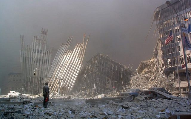 Sur cette photo d'archives prise le 11 septembre 2001, un homme se tient debout dans les décombres et demande si quelqu'un a besoin d'aide, après l'effondrement de la première tour du World Trade Center à New York City. (Crédit :  DOUG KANTER / AFP)