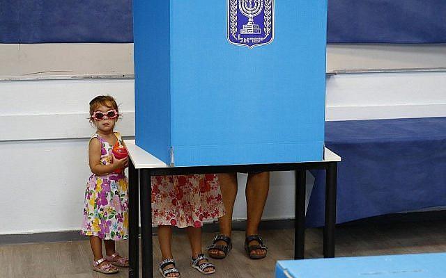 Des enfants israéliens accompagnent leurs parents dans les bureaux de vote de Rosh HaAyin, le 17 septembre 2019. (Crédit : Jack GUEZ/AFP)