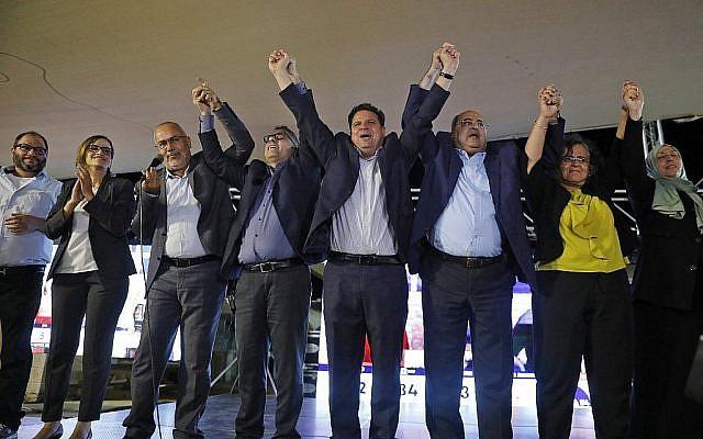 (G à D) Ofer Cassif, Heba Yazbak, Osama Saadi, Mtanes Shehadeh, Ayman Odeh, Ahmad Tibi, Aida Touma et Iman Khatib Yassin, devant leurs partisans au siège de campagne de l'alliance à Nazareth, dans le nord d'Israël, le 17 septembre 2019, à l'annonce des premiers sondages de sortie des urnes à la télévision. (Crédit : Ahmad GHARABLI / AFP)