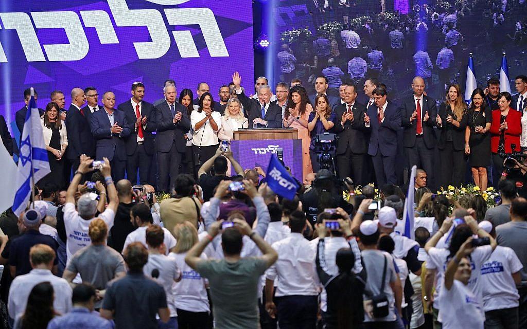 Le Premier ministre israélien Benjamin Netanyahu (C) fait un signe de la main alors qu'il s'adresse à des partisans au siège de la campagne électorale de son parti, le Likud, le 18 septembre 2019. (Crédit : Jack GUEZ / AFP)