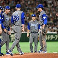 Les joueurs israéliens et un coach autour du joueur Josh Zeid (#28) pendant le match entre Israël et le Japon au Dôme de Tokyo à Tokyo, le 15 mars 2017 (Crédit : AFP PHOTO / TORU YAMANAKA)
