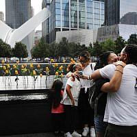 Des enfants de victimes, tuées le 11 septembre 2001, s'étreignent au National September 11 Memorial pendant une cérémonie commémorative du matin pour les victimes des attaques terroristes 18 ans après, le 11 septembre 2019 à New York City. Dans tout le pays, des cérémonies ont été organisés pour commémorer les 2977 personnes tuées à New York, au Pentagone et dans un champ en Pennsylvanie. New York, le 11 septembre 2019. (Spencer Plate/Getty Images/AFP)