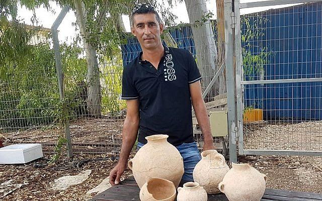 Ahmed Nassar Yassin avec les artéfacts vieux de 4500 ans qu'il a découverts dans une grotte funéraire près d'Araba, dans le nord d'Israël (Crédit : Nir Distelfeld/Autorité israélienne des antiquités)
