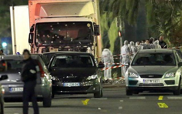 Les experts médico-légaux près d'un camion dont le pare-brise est criblé de balles après un attentat contre la foule venue voir le feu d'artifice lors de la fête nationale dans la ville de Nice, le 15 juillet 2016 (Crédit : AP Photo/Claude Paris)