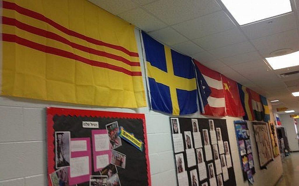 Le couloir de l'école communautaire Hershorin Schiff de Sarasota, en Floride, décoré des 40 drapeaux représentant les pays dont les familles des élèves sont originaires (Crédit : Ben Sales/JTA)