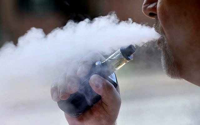 Un homme expulse de la fumée après avoir actionné sa cigarette électronique à Portland, dans le Maine, le 28 août 2019. (Crédit : AP/Robert F. Bukaty, File)