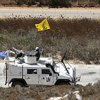 Les forces de maintien de la paix espagnoles de l'ONU patrouillant sur la frontière israélo-libanaise passent devant un drapeau du Hezbollah, dans le village de Kfar Kila, dans le sud du Liban, le 2 septembre 2019 (Crédit :  AP Photo/Hussein Malla)