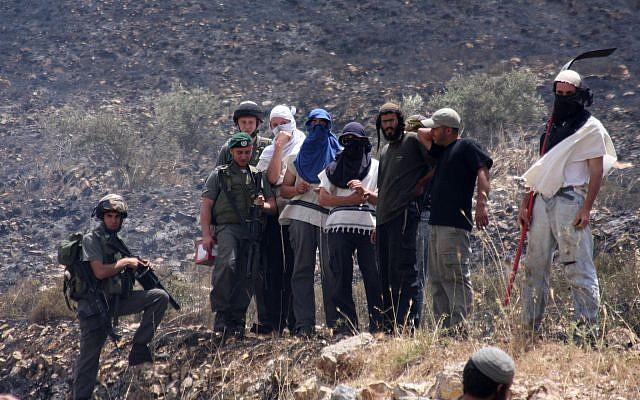 Des résidents de Yitzhar masqués et des soldats surveillent les champs palestiniens incendiés dans le village d'Asira al-Qiblyia le 2 juin 2010. (Wagdi Ashtiyeh/Flash90)