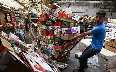 Des employés recyclent les cartons de fruits et de légumes au marché Mahane Yehuda de Jérusalem, le 25 juin 2015 (Crédit :  Nati Shohat/FLASH90)
