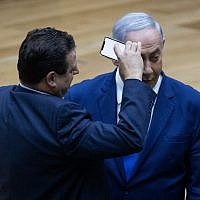 Le leader de la Liste arabe unie, Ayman Odeh, filme le Premier ministre Benjamin Netanyahu pendant le débat sur le projet de loi des caméras à la Knesset de Jérusalem, le 11 septembre 2019 (Crédit : Yonatan Sindel/Flash90)