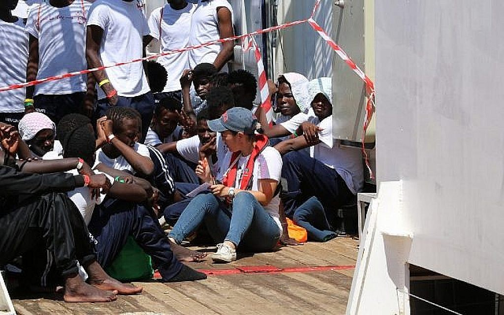 Une secouriste avec des réfugiés à bord de l'Ocean Viking, au mois d'août 2019 (Crédit : Hannah Wallace Bowman/SOS Méditerranée)