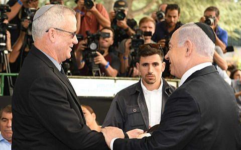 Benjamin Netanyahu et Benny Gantz échange une poignée de main durant évènement marquant le troisième anniversaire de la mort du président Shimon Peres, le 19 septembre 2019 (Crédit : GPO)