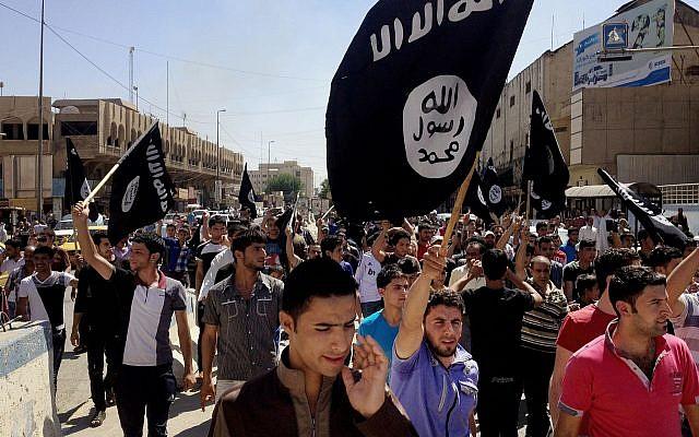 Dans cette photo du 16 juin 2014, des manifestants scandent des slogans pro Etat islamique alors qu'ils portent des drapeaux du groupe devant le siège du gouverne-ment provincial à Mosul, en Irak (AP Photo)