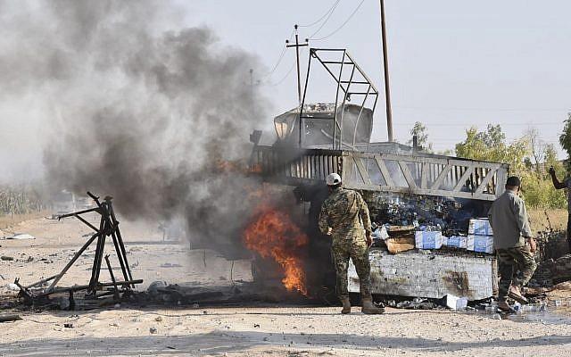Des membres des Unités de mobilisation populaire se tiennent à côté d'un camion en feu après une attaque de drone imputée à Israël, à proximité du point de passage Qaim, dans la province Anbar, en Iraq, le 25 août 2019. (AP Photo)