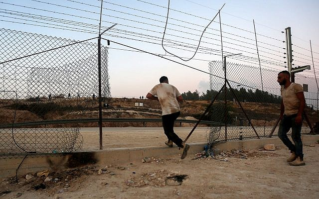 Des Palestiniens traversent illégalement une barrière de sécurité pour entrer en Israël autour de la ville d'Hébron en Cisjordanie, le 6 août 2019. (Wisam Hashlamoun/Flash90)