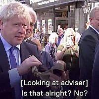 Le Premier ministre britannique Boris Johnson tente de souffler dans un shofar dans une vidéo publiée le 13 décembre 2019. (Capture d'écran : Channel 5 News)