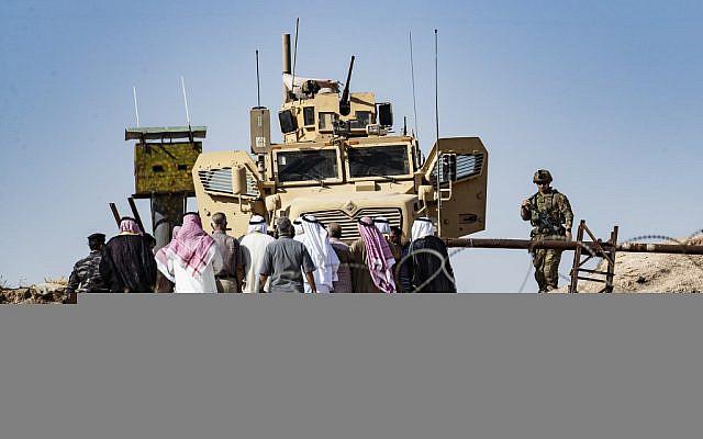 Des Kurdes syriens lors d'une manifestation contre les menaces turques sur une base de la coalition internationale dirigée par les Américains près de Ras al-Ain, dans la province de Hasakeh, en Syrie, le 6 octobre 2019 (Crédit : Delil SOULEIMAN / AFP)