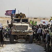 Les Kurdes syriens se réunissent autour d'un blindé américain durant une manifestation contre les menaces de la Turquie près d'une base de la coalition internationale dirigée par les Etats-Unis aux abords de Ras al-Ain, dans la province de Hasakeh, en Syrie, près de la frontière turque, le 6 octobre 2019. (Crédit: Delil Souleiman/AFP)