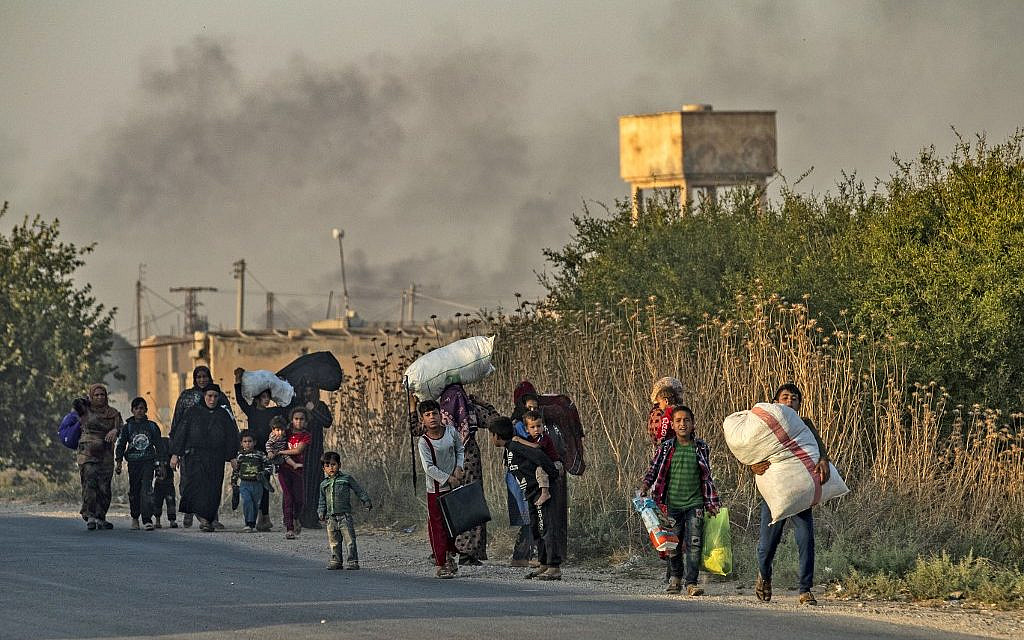 Des civils syriens arabes et kurdes fuient avec leurs biens au milieu des bombardements turcs sur la ville de Ras al-Ain, au nord-est de la Syrie, le 9 octobre 2019. (Delil SOULEIMAN / AFP)