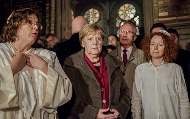 La chancelière allemande Angela Merkel (centre) parle avec la rabbin Gesa Ederberg (gauche) et d'autres membres de la communauté juive lors d'une veillée devant la Nouvelle Synagogue à Berlin le 9 octobre 2019. (Photo d'Anton Roland LAUB / AFP)