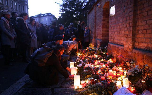 Des bougies allumées devant la synagogue de Halle, à l'est de l'Allemagne, 24 heures après une fusillade antisémite, le 10 octobre 2019. (Crédit : Ronny Hartmann / AFP)