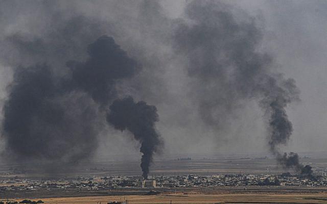 De la fumée monte de la ville syrienne de Ras al-Ain, sur une photo prise du côté turc de la frontière à Ceylanpinar le 11 octobre 2019, le troisième jour de l'opération militaire turque contre les forces kurdes. (Crédit : Ozan KOSE / AFP)